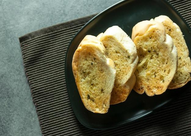 Rebanadas de pan de ajo y hierbas sobre la mesa, sabroso pan con ajo