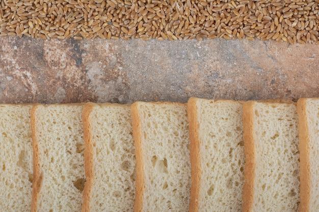 Rebanadas de pan blanco con cebada sobre fondo de mármol