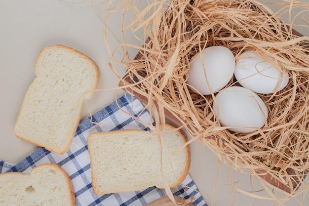 Rebanadas de pan blanco fresco con huevos sobre un mantel
