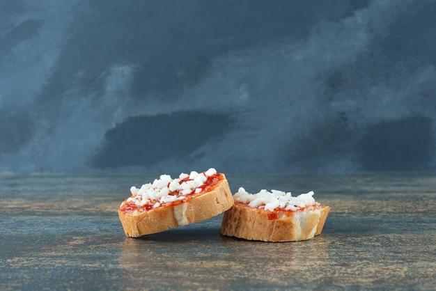 Rebanadas de pan blanco fresco con mermelada sobre fondo de mármol