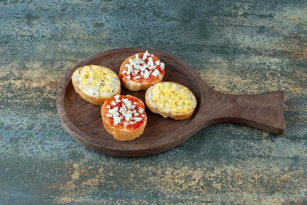Rebanadas de pan blanco fresco con mermelada sobre tabla de madera
