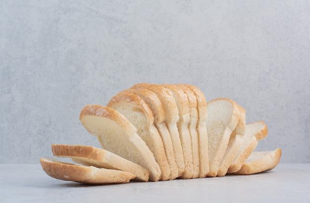 Rebanadas de pan blanco fresco sobre fondo de mármol.