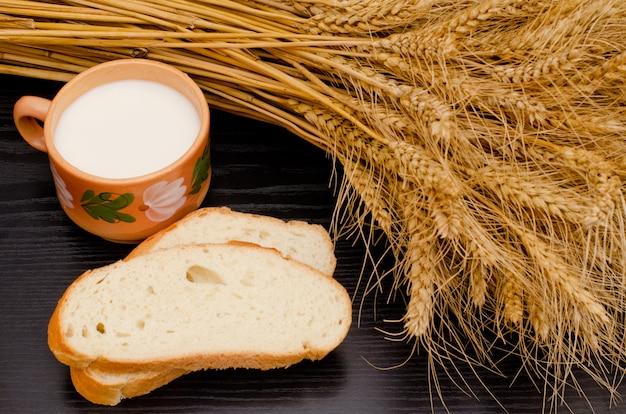 Rebanadas de pan blanco, una taza de leche y espigas en una mesa negra, vidsverhu, primer plano
