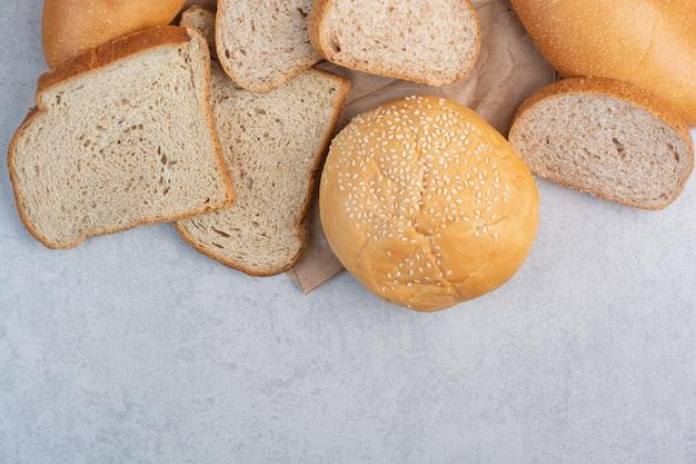 Rebanadas de pan y bollo con semillas de sésamo en hoja de papel. foto de alta calidad