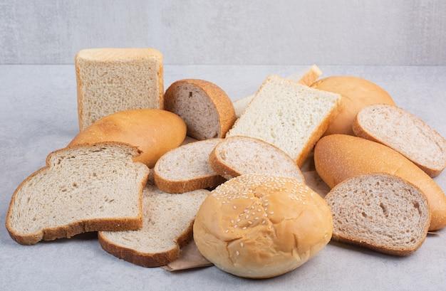 Rebanadas de pan y bollo con semillas de sésamo en hoja de papel