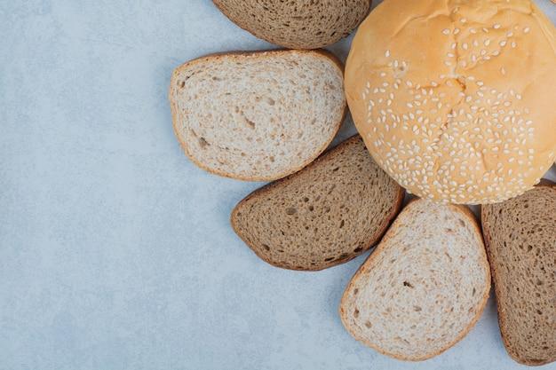 Rebanadas de pan y bollo con semillas de sésamo sobre fondo azul. foto de alta calidad