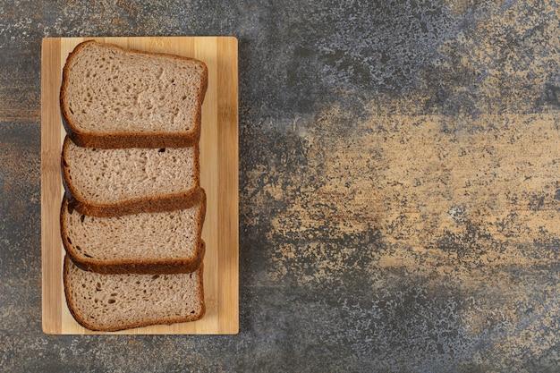 Rebanadas de pan de centeno fresco sobre tabla de madera.