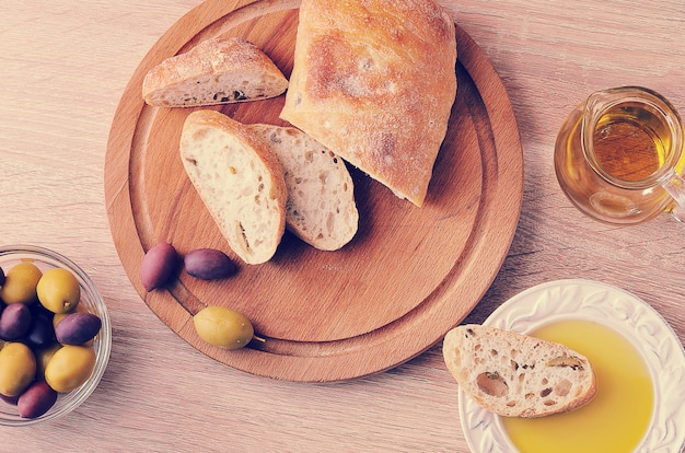 Rebanadas de pan de chapata, aceitunas y aceite de oliva virgen extra