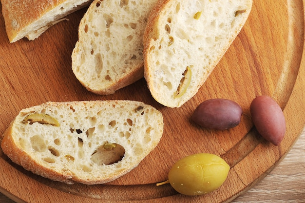 Rebanadas de pan de chapata en una tabla redonda, aceitunas