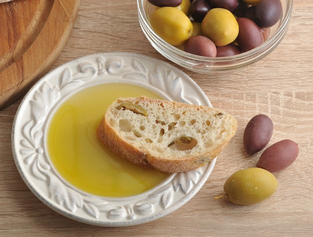 Rebanadas de pan ciabatta sobre tabla redonda, aceitunas y aceite de oliva virgen extra