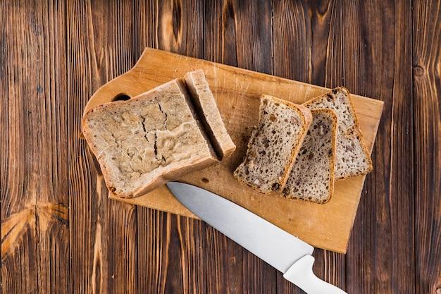 Rebanadas de pan y cuchillo afilado en tajadera