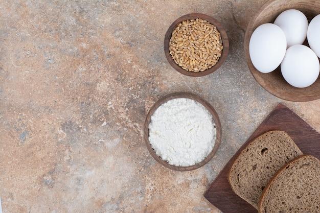 Rebanadas de pan, cuencos de huevos, harina y cebada sobre superficie de mármol