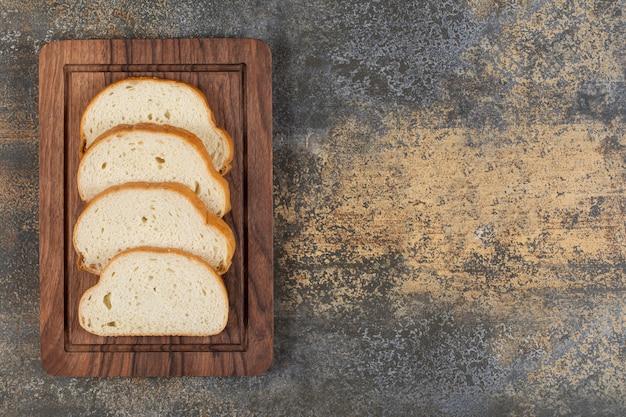 Rebanadas de pan fragante sobre plancha de madera