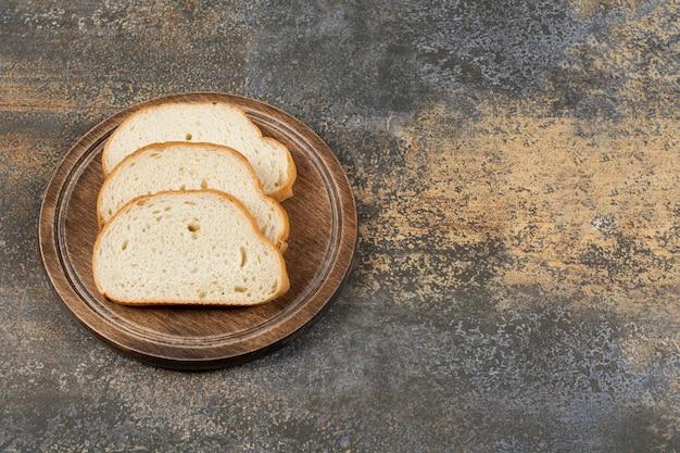 Rebanadas de pan fragante sobre tabla de cortar de madera