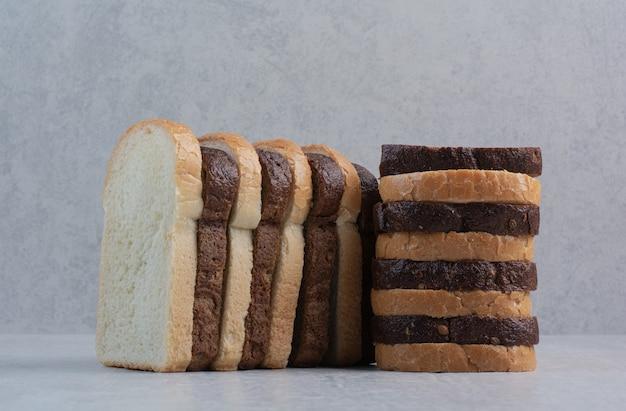 Rebanadas de pan fresco blanco y marrón sobre fondo de mármol.