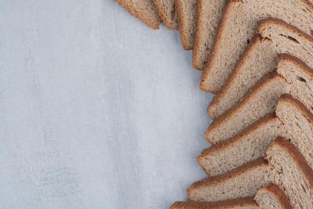 Rebanadas de pan fresco marrón sobre fondo de mármol.