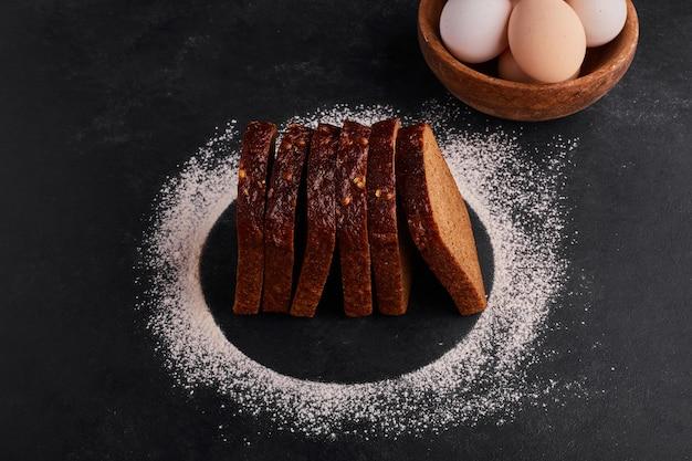 Rebanadas de pan con harina y huevos alrededor.