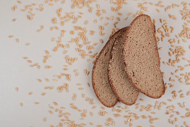 Rebanadas de pan integral fresco con granos de avena sobre superficie blanca
