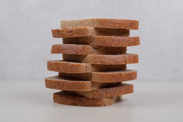 Rebanadas de pan integral fresco sobre superficie blanca