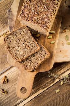 Rebanadas de pan integral de grano con semillas de girasol en la tabla de cortar