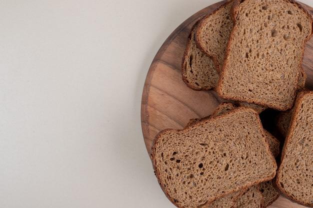 Rebanadas de pan integral en placa de madera. foto de alta calidad