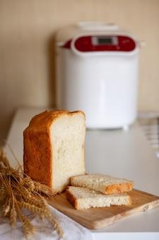 Rebanadas de pan de una máquina de hacer pan con espiguillas de trigo sobre una tabla con una servilleta de cocina