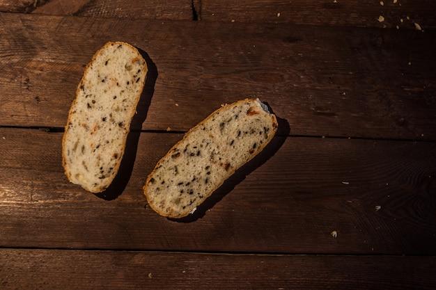 Rebanadas de pan marrón en una mesa de madera. pan de testigo con salvado y cereales