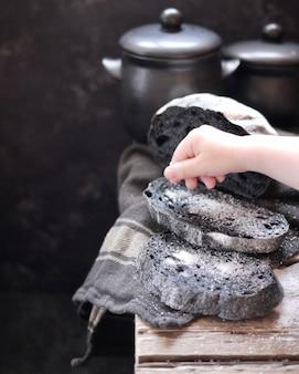 Rebanadas de pan negro con la adición de carbón activado. rebanadas de pan con sal en una mesa de madera. niño que sala un pedazo de pan