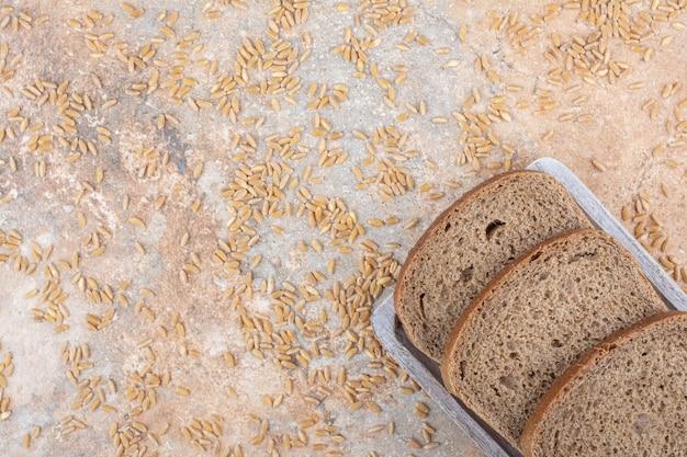Rebanadas de pan negro con granos de cebada sobre superficie de mármol