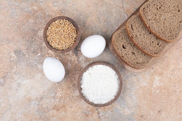 Rebanadas de pan negro, harina, cebada y huevos sobre superficie de mármol