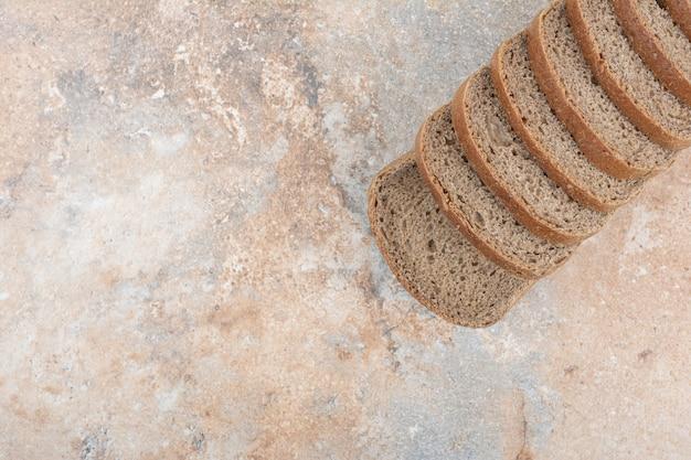 Rebanadas de pan negro sobre fondo de mármol