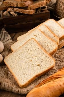 Rebanadas de pan oscuro y blanco en caja y sobre mantel