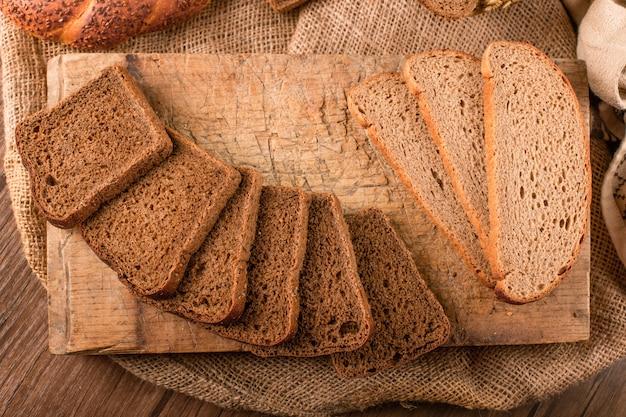 Rebanadas de pan oscuro y blanco en la tabla de la cocina