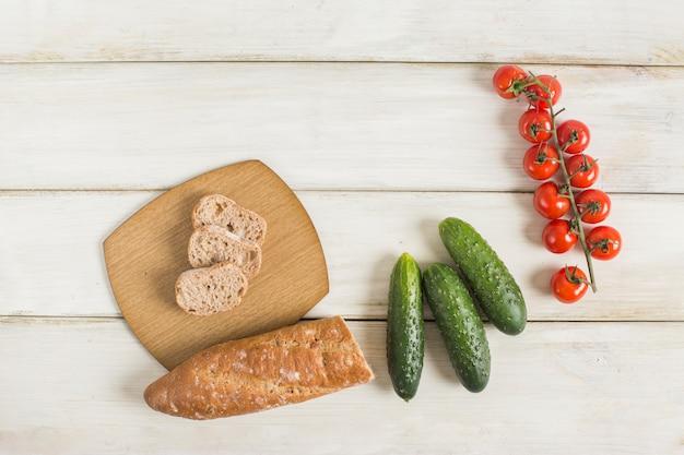 Rebanadas de pan; pepino y tomates cherry rojos en mesa de madera