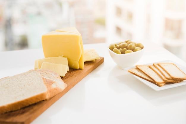 Rebanadas de pan con queso y aceitunas en mesa blanca