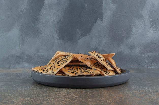 Rebanadas de pan recubierto de sésamo apilados en una cacerola pequeña para servir