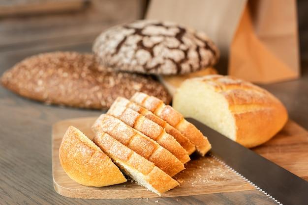Rebanadas de pan sobre la mesa sobre un fondo de varios panes.