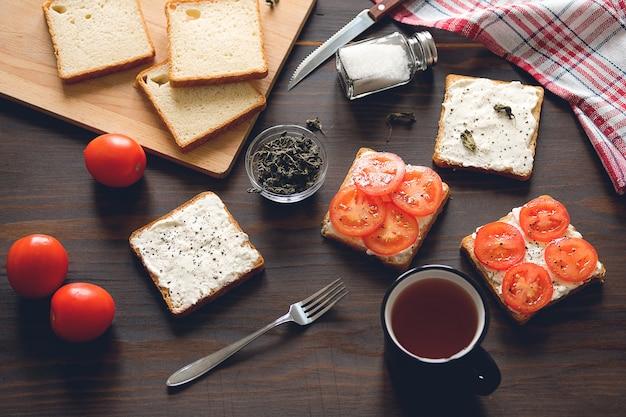 Rebanadas de pan, una taza de té, sándwiches con queso y tomate, en una mesa de madera. productos agrícolas orgánicos.