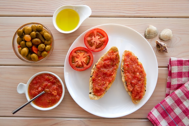Rebanadas de pan tostado con tomate rallado.