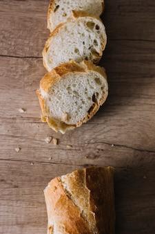Rebanadas de panes frescos en el fondo de madera