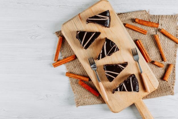 Rebanadas de pastel de chocolate con palitos de canela en una tabla de madera y un saco sobre fondo blanco, endecha plana.
