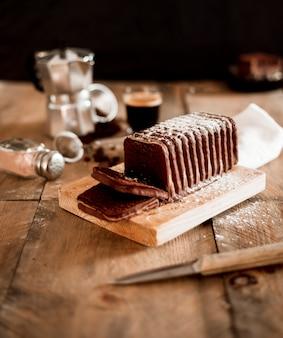 Rebanadas de pastel de chocolate en tabla de cortar de madera sobre la mesa