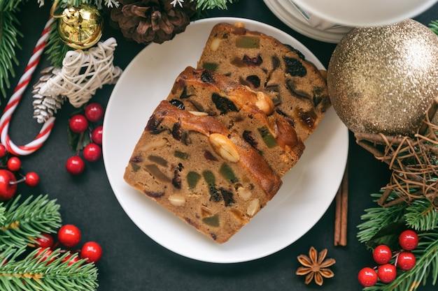 Rebanadas de pastel de fruta dulce en plato blanco sobre mesa de granito negro en la vista superior plana con decoración navideña.