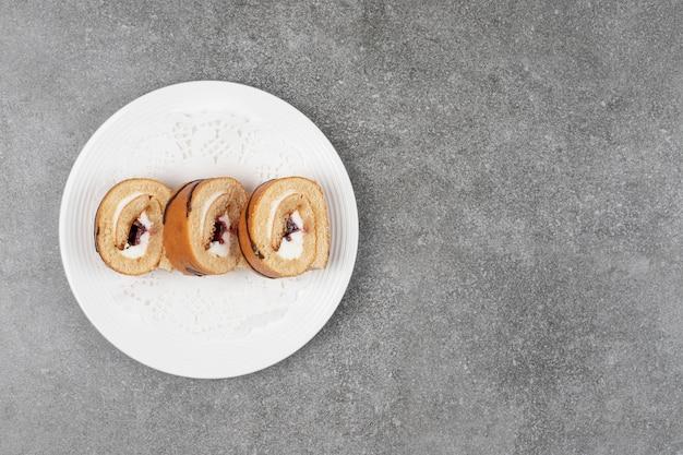 Rebanadas de pastel de rollo dulce en la placa blanca.