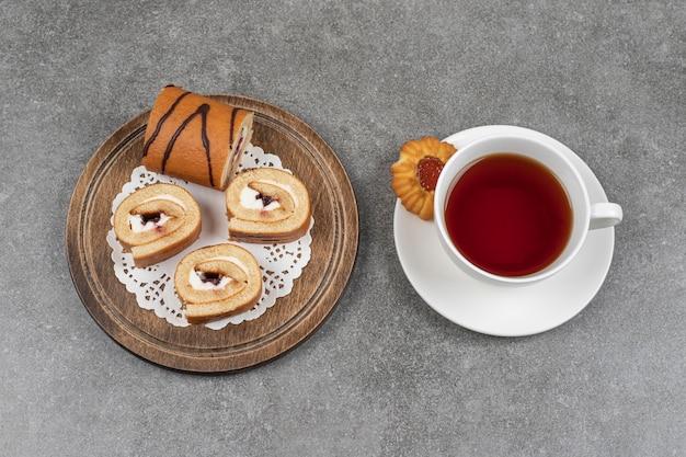 Rebanadas de pastel de rollo dulce sobre tabla de madera con taza de té
