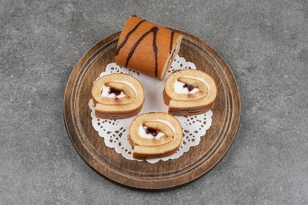 Rebanadas de pastel de rollo dulce sobre tabla de madera