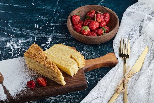 Rebanadas de pastel con una taza de fresas.