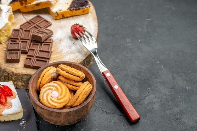 Rebanadas de pastel de vista frontal con chocolate y galletas sobre fondo oscuro