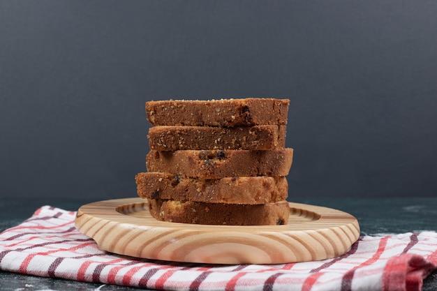 Rebanadas de pasteles de cebra y pasas en placa de madera.