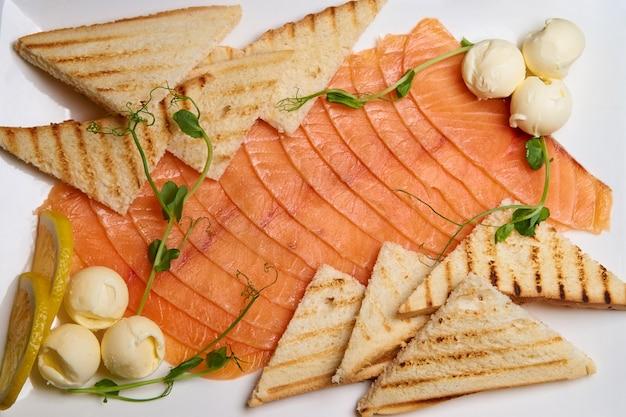Rebanadas de pescado con pan tostado y mantequilla en un plato blanco.